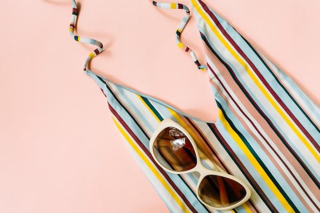 ストライプの水着、ピンクの背景にサングラス、フラットレイ。女性のビーチアクセサリー。夏の背景。旅行のコンセプト。上面図。高品質の写真