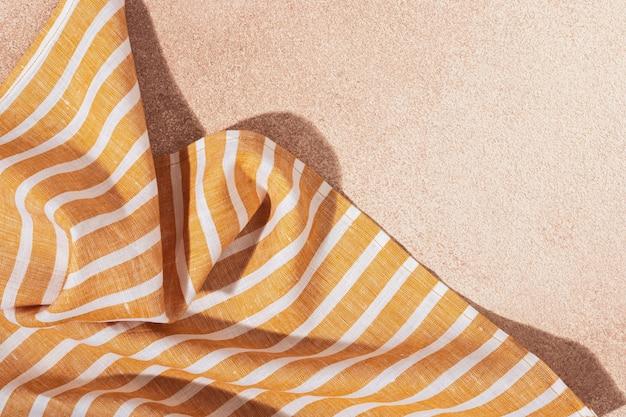 베이지색 회 반죽 배경에 줄무늬 섬유 노란색 서빙 냅킨