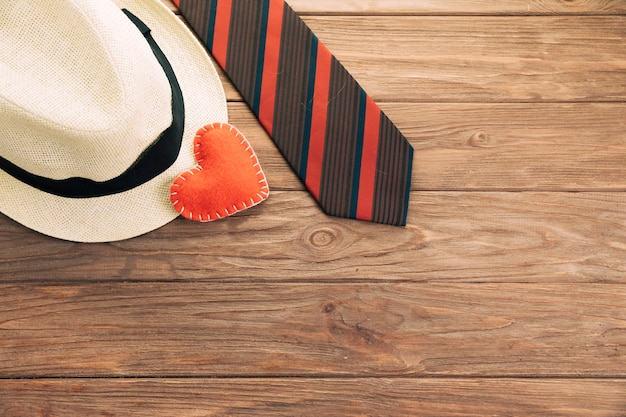 Striped tie near hat and heart on board