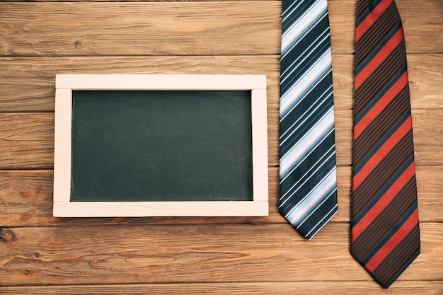 Striped ties on board near blackboard