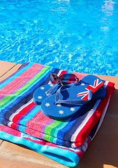 プールの冷たい青い水の近くの縞模様のタオルとサンダル