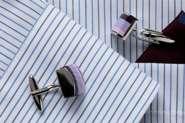 Полосатая бело-синяя мужская рубашка с разноцветными запонками. деловой дресс-код. крупный план. выберите фокус.
