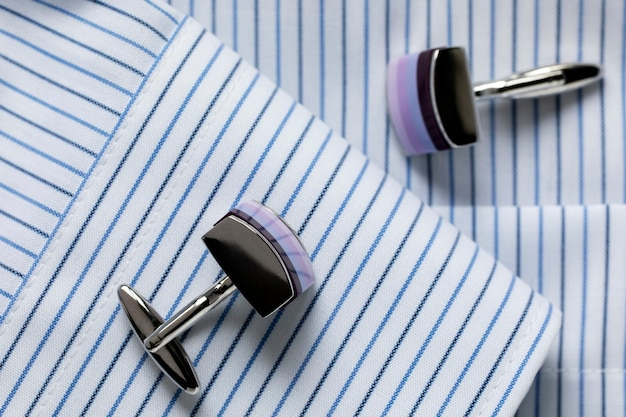 Striped white and blue men's shirt close up with multicolored cufflinks. close-up. selecrive focus.