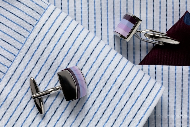 Striped white and blue men's shirt with multicolored cufflinks. business dress code. close-up. selecrive focus.