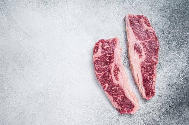 스트립로인 스테이크 또는 뉴욕 스테이크, 생 쇠고기 도살 고기 컷. 흰 바탕. 평면도. 공간을 복사합니다.