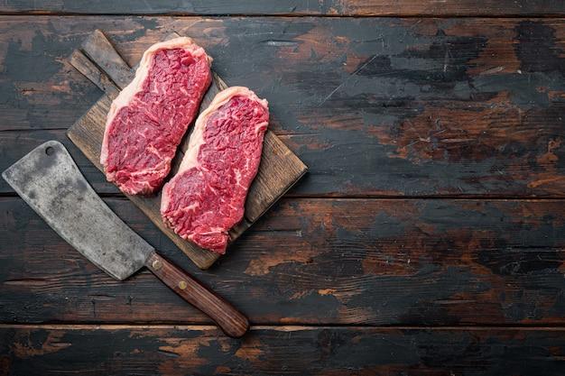 Striploin 스테이크, 원시 쇠고기 도살 컷, 오래 된 나무 테이블, 상위 뷰, 텍스트 복사 공간