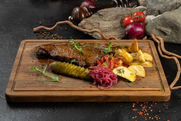 Striploin steak with potatoes. meat main course with beef, baked potatoes and pickled vegetable appetizers