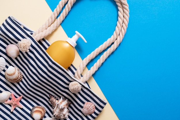 Stripped beach bag with sunscreen cream and seashell.