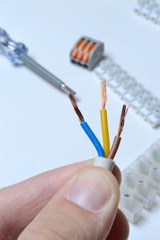 端子台と工具の背景に対して、手に剥がされた電気3芯線。閉じる。