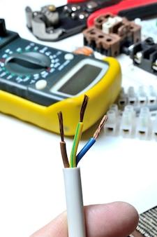 端子台と工具の背景に対して、手に剥がされた電気3芯線。閉じる。 Premium写真