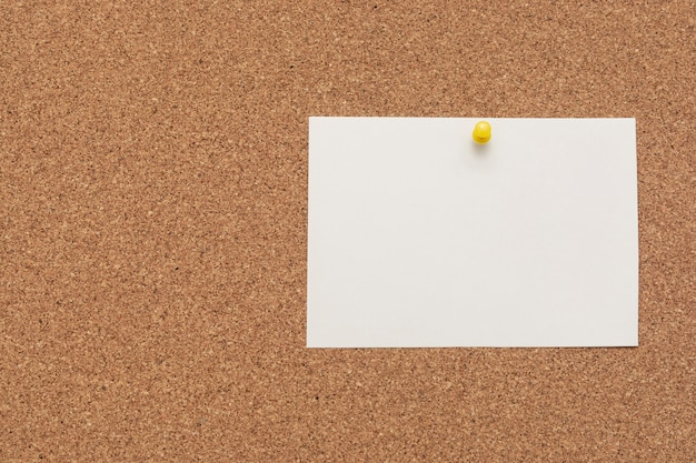 Stripped note paper with push pin on cork board