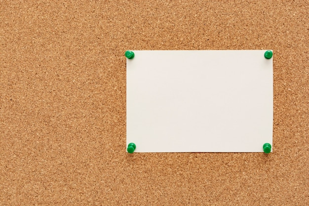 Stripped note paper with push pins on cork board