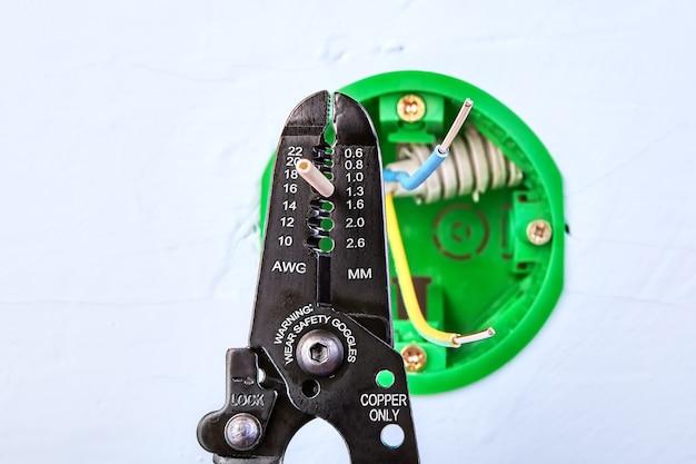 Зачистка концов проводов круглой коробки для выключателя настенного света.