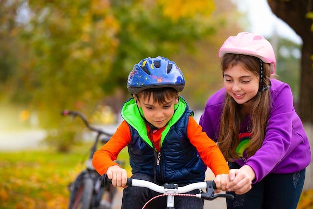 Стремление к успеху. сестра учит своего младшего брата кататься на велосипеде в парке. осень. семья и здоровый образ жизни.