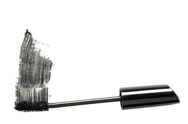 Stroke of black mascara with applicator brush close-up isolated on white