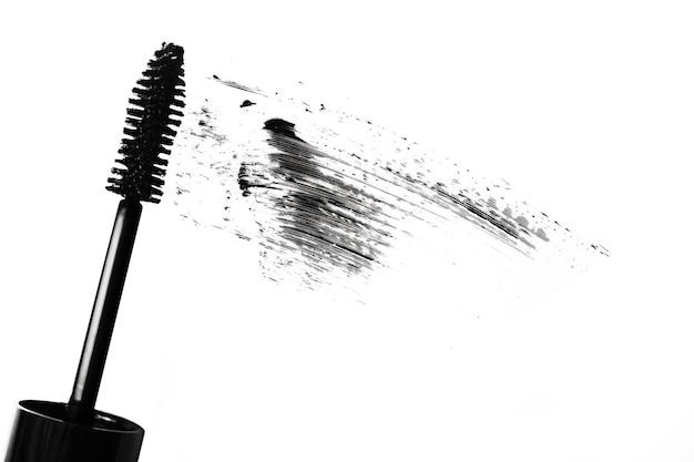 Stroke of black mascara with applicator brushflat laysmear of make upisolated on white