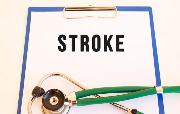 Инсульт - текст на медицинской папке с документами и стетоскопом на белом фоне. медицинская концепция.