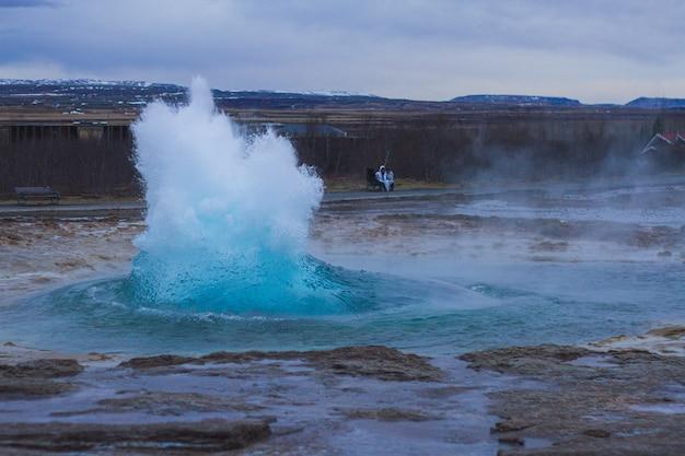 アイスランドの夕方に曇り空の下の丘に囲まれたストロックル間欠泉