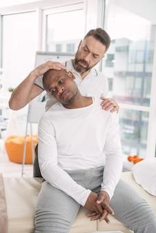 強い痛み。深刻な悲しい男が肩の痛みを抱えながら医師を訪問