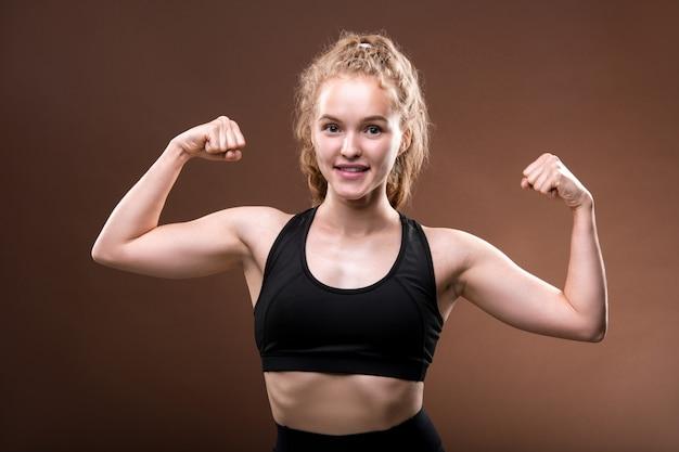 Сильная активная молодая спортсменка в черном спортивном костюме делает жест, демонстрирующий ее физическую силу, стоя в изоляции