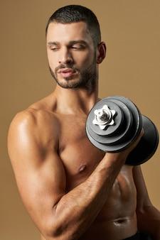 Сильный взрослый спортсмен-мужчина с мощным торсом позирует со специальным инструментом перед фотоаппаратом
