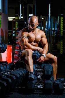 Сильный, взрослый, подтянутый, мускулистый мужчина-тренер позирует для фотосессии в спортзале в спортивной одежде, демонстрируя свои мускулы.