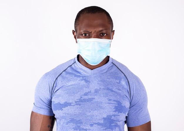 Сильный человек афроамериканца нося коронавирусную медицинскую маску, изолированную белую предпосылку