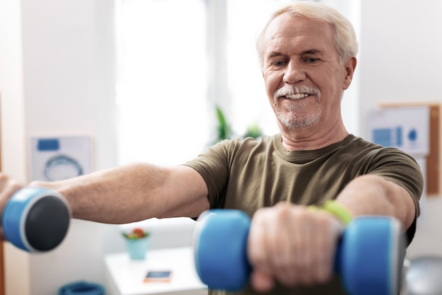 Strong again. nice senior man looking at his hands with dumbbells while feeling strength in them