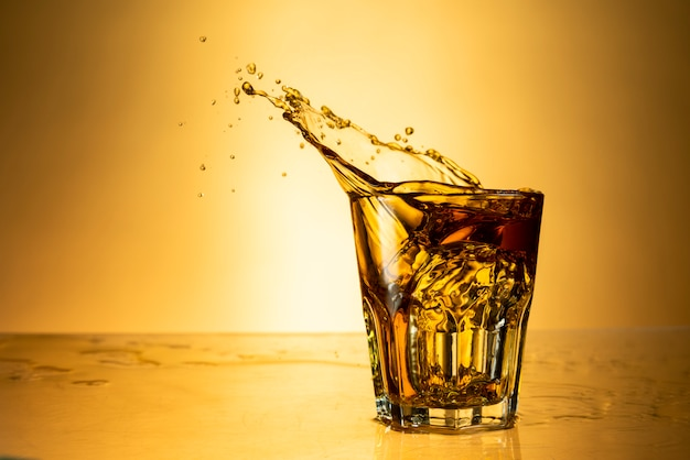 Strong alcohol in a glass with splash on a background of yellow background with reflection