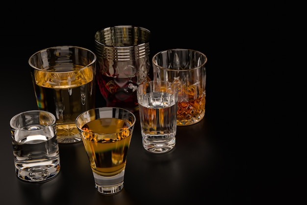 Strong alcoholic drinks, in glasses on a dark background