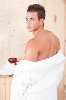サウナやスパでのボディトリートメントの後、タオルを持った強くて魅力的な若い男