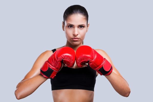 強くて美しい。灰色の背景に立っている間アートカメラを探しているボクシンググローブの美しい若いスポーティな女性