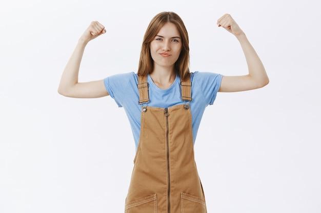 Сильная и уверенная милая девушка показывает мышцы, сгибает бицепсы, хвастается силой