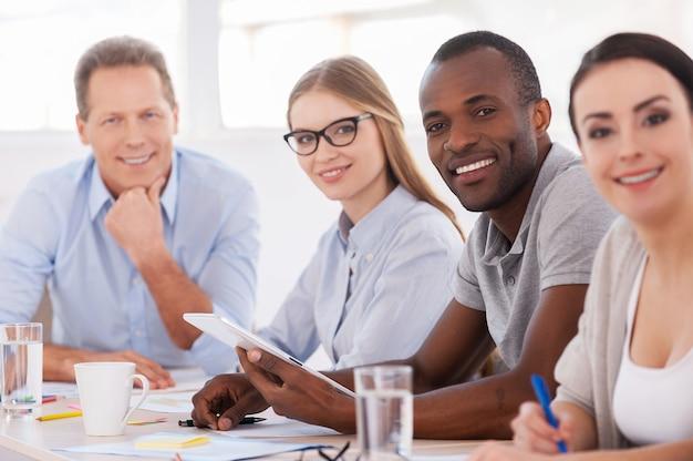 Сильный и творческий коллектив. группа деловых людей, сидящих в ряд за столом и улыбающихся в камеру