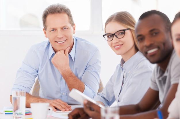 Сильный и творческий руководитель команды. уверенный зрелый мужчина сидит за столом, пока его коллеги сидят в ряду и смотрят в камеру