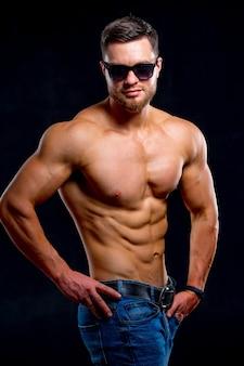 強くてフィットする男のボディービルダー。スポーティな筋肉質の男のアスリート。スポーツとフィットネスのコンセプト。男性の力。