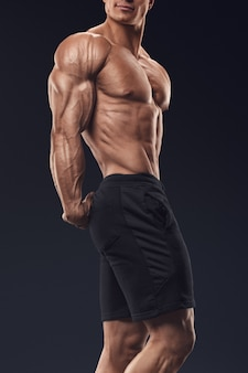 Сильный и красивый молодой культурист демонстрирует свои мускулистые