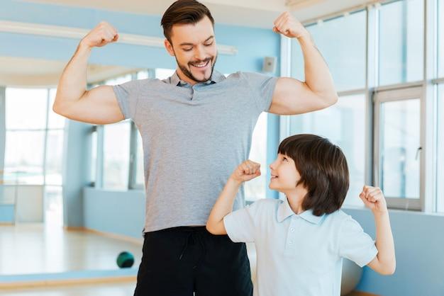 強くて健康的。幸せな父と息子がヘルスクラブに立っている間、上腕二頭筋を見せて笑顔を見せています