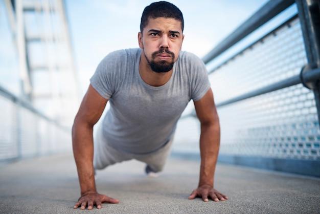 Сильный и высокомотивированный спортсмен делает отжимания