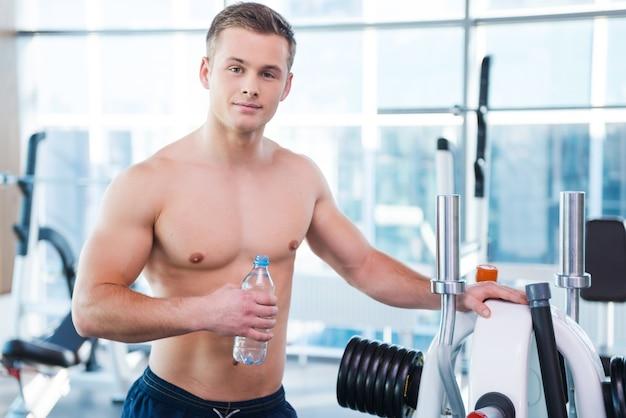 강하고 근육질입니다. 물병을 들고 체육관에 서 있는 동안 카메라를 바라보는 자신감 있는 젊은 근육질의 남자