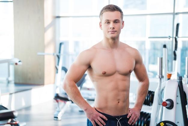 強くて筋肉質。腰に手をつないで、ジムに立っている間カメラを見て自信を持って若い筋肉の男