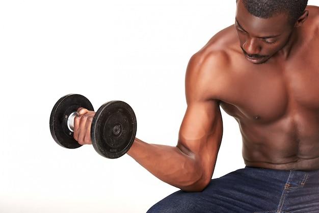 白で隔離されるダンベルと強いと筋肉の男