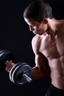 Сильный и мускулистый парень с гантелями