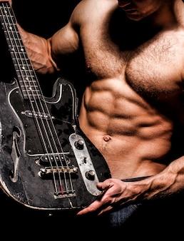 Сильный и мускулистый мужчина держит гитару