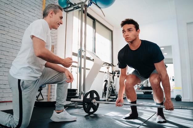 パーソナルトレーナーのモチベーションでウェイトリフティング腕のエクササイズをしている20代の強くて筋肉質の若い男