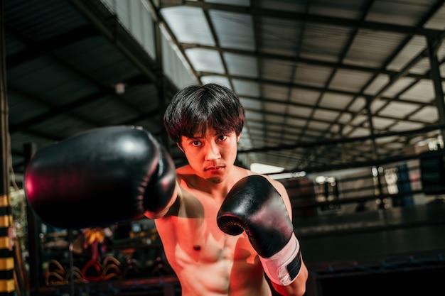 권투 장비에 강하고 근육질의 젊은 남자가 권투 훈련장에서 옆에 copyspace와 타격 모션을