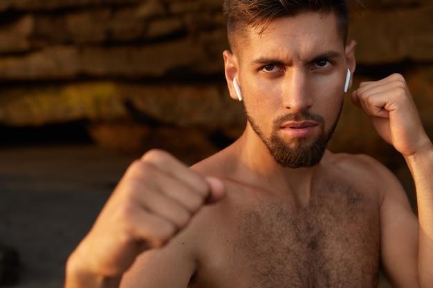 강력한 화난 권투 선수가 수비 제스처로 포즈를 취하고 주먹을 움켜 쥔다.