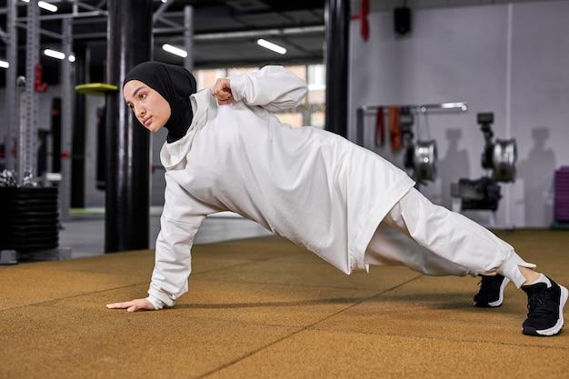 片方の腕で腕立て伏せをし、一人でトレーニングし、トレーニングエクササイズをし、クロスフィットのコンセプトを行う強いアラビアのスポーツウーマン。フィットネスセンターで