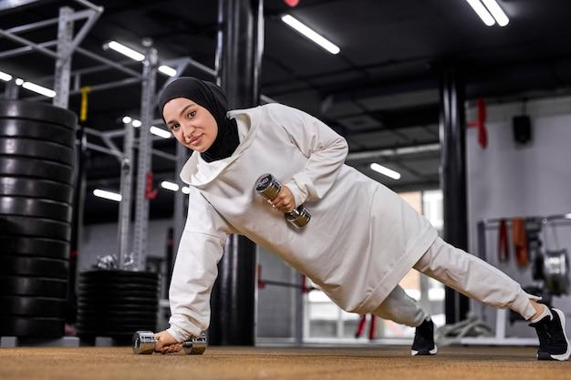 Сильная арабская спортсменка делает отжимания одной рукой, тренируется в одиночку с гантелями, выполняет упражнения, концепция кроссфита. в фитнес-центре