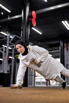 片方の腕で腕立て伏せをし、ダンベルを使って一人でトレーニングし、トレーニングエクササイズをし、クロスフィットのコンセプトを行う強いアラビアのスポーツウーマン。フィットネスセンターで